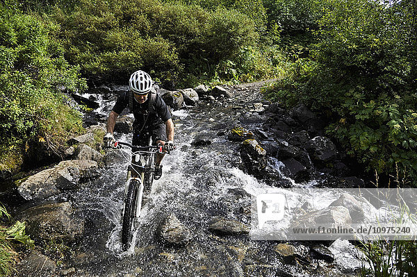 Man rides a full suspension mountain bike across a stream on the Devil's Pass Trail in the Chugach National Forest  Kenai Peninsula  South-central Alaska