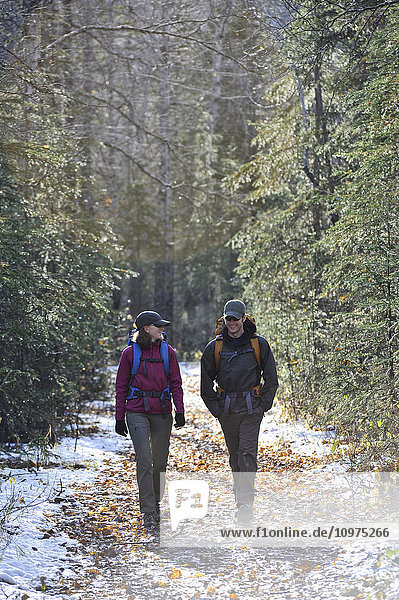 Backpacking couple walks the Albert Loop Trail in Chugach State Park near the Eagle River Nature Center in Southcentral Alaska