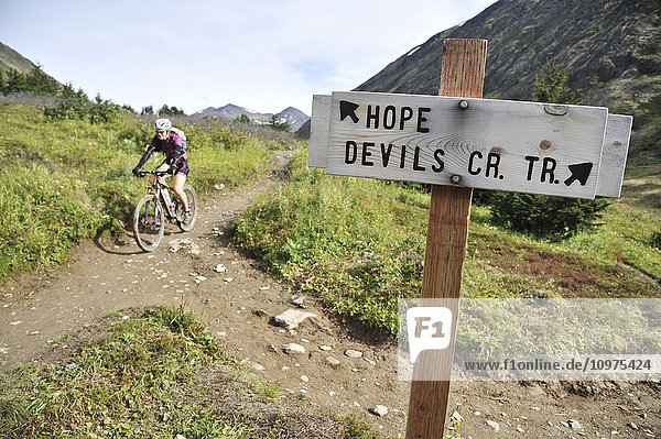 Woman rides a full suspension mountain bike on the Devils Pass Trail in the Chugach National Forest  Kenai Peninsula  Southcentral Alaska