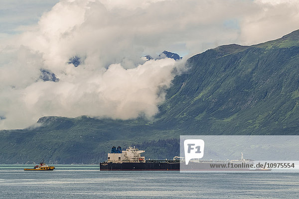 Tug boats work in Port Valdez moving a large ship around  Southcentral Alaska