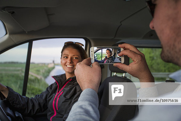 'A man takes a photograph of a young woman with a smart phone while sitting in a vehicle; Egmond aan Zee  Holland'