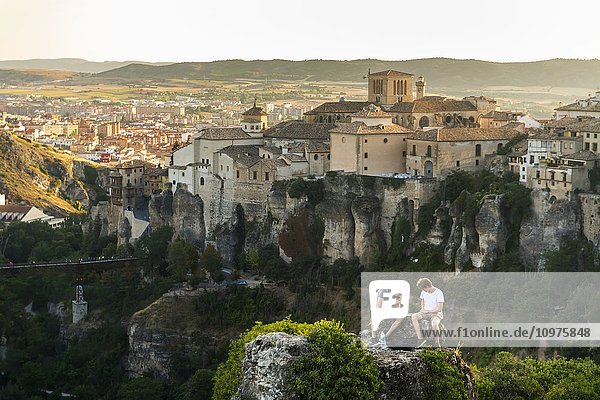 'Two friends having rest in the surroundings of Cuenca with a beautiful landscape behind them; Cuenca  Castile-La Mancha  Spain'