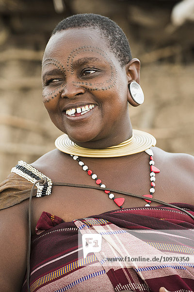 'Portrait of Datoga woman with tattooed face and wearing traditional clothing and jewelry  near Lake Eyasi; Tanzania'