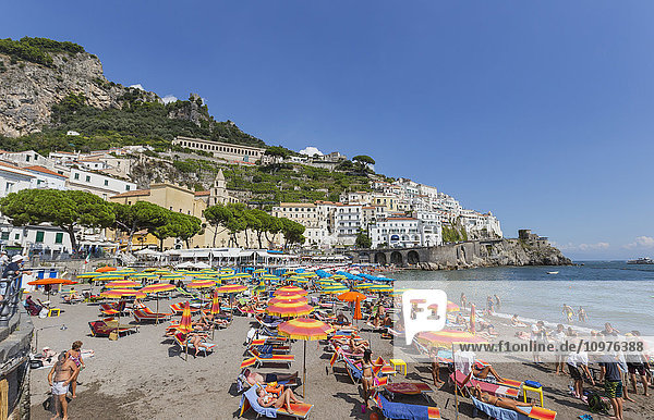 'The beach view from the board walk in the town of Amalfi Italy  where tourists enjoy the sunlight and views of the Mediterranean Sea; Amalfi  Province of Salerno  Italy'