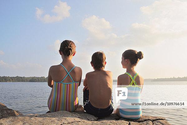 'Kids sitting on rock at edge of Crystal Lake; Ontario  Canada'