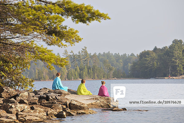 'Kids wrapped in towels sitting on rock at edge of Crystal Lake; Ontario  Canada'
