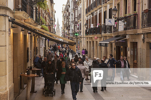 'A view down Calle Major towards the cathedral with crowds of people strolling around; San Sebastian  Spain'