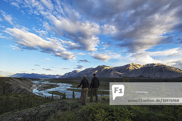 'Woman and man looking out at the Wind River in the Peel Watershed; Yukon  Canada'