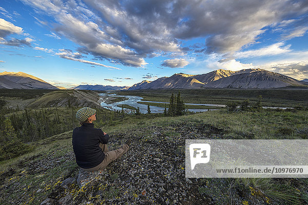'Woman sitting on a rock looking out at the Wind River in the Peel Watershed; Yukon  Canada'
