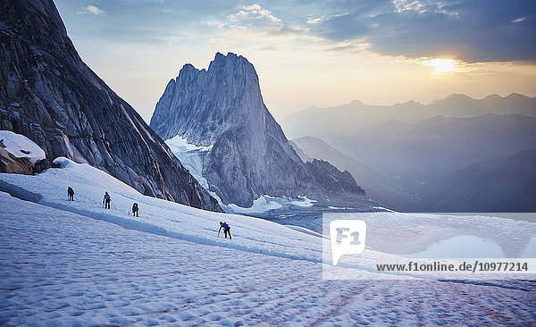 'Hiking around a crevice of West Ridge of Pigeon Spire route in the Bugaboos Provincial Park at dawn; British Columbia  Canada'
