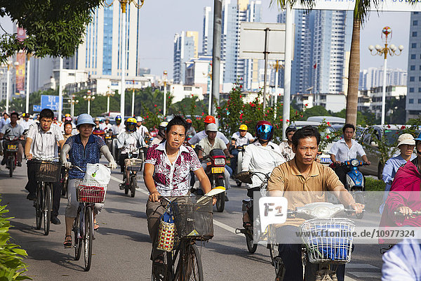 'People commuting in the early morning on bicycles and scooters in a separate lane; Nanning  Guangxi  China'