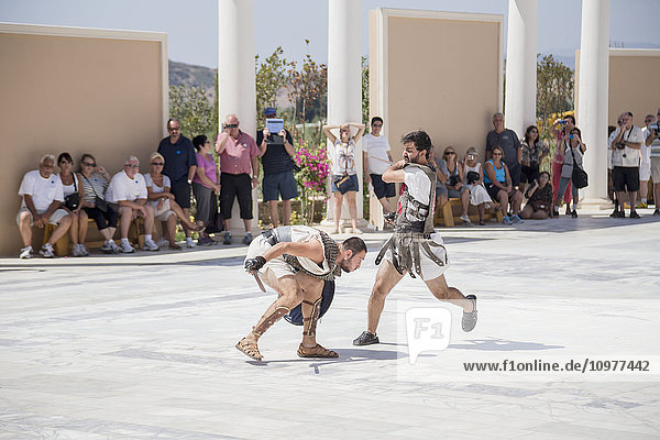 'A pair of actors dressed as gladiators fight in a duel in front of a crowd of tourists at a Greek history attraction in Turkey; Kusadasi  Izmir  Turkey'