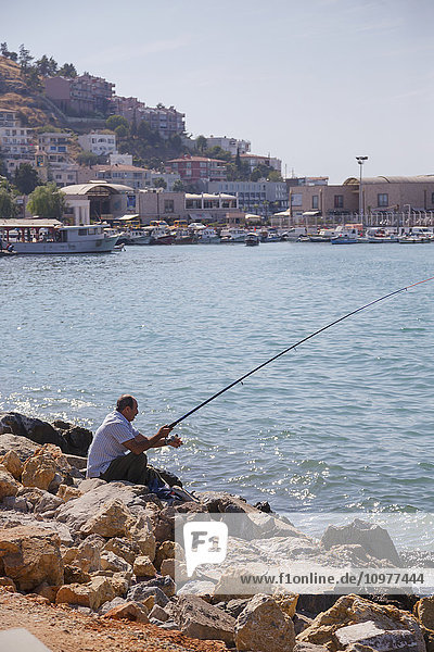 'A middle aged man sits on a rock fishing on the Mediterranean Sea on a sunny summer day; Kusadasi  Izmir  Turkey'