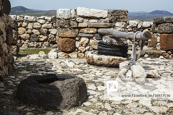 'Olive press and stone basin at the site of ancient ruins; Tel Hazor  Israel' 'Olive press and stone basin at the site of ancient ruins; Tel Hazor, Israel'
