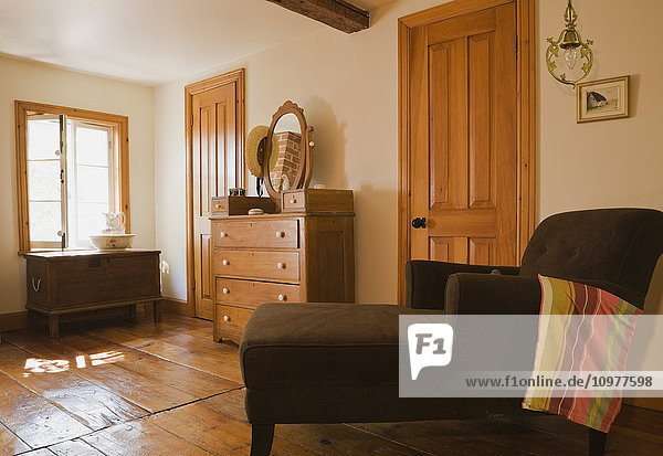 Long Chair And Antique Chest With A Mirror In The Upstairs Master Bedroom Of An Old Canadiana (Circa 1741) Cottage Style Wooden Siding Residential Home  Quebec  Canada. This Image Is Property Released For Calendar  Book  Magazine And Editorial Use Only. L