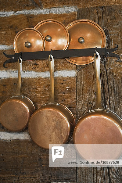 Close-Up Of A Copper Cooking Pots And Lids On The Kitchen Wall Made Of Logs In An Old Reconstructed 1983 Canadiana Cottage Style Residential Log Home  Quebec  Canada. This Image Has A Property Release. Pr0088