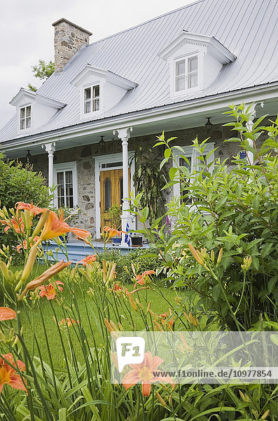 Old Canadiana Cottage Style Residential Home Through Flowers And Shrubs  Quebec  Canada. This Image Is Property Released. Pr0131