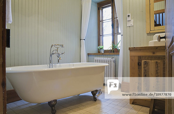 Bathroom With A Roll Top Bathtub In An Old Canadiana (Circa 1832) Cottage Style Residential Fieldstone Home  Quebec  Canada. This Image Is Property Released For Calendar  Book  Magazine And Editorial Use Only. Lupr0175
