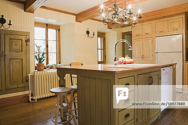 Partial View Of The Kitchen With An Island Containing The Sink And Dishwasher In An Old Canadiana (Circa 1832) Cottage Style Residential Fieldstone Home  Quebec  Canada. This Image Is Property Released For Calendar  Book  Magazine And Editorial Use Only.