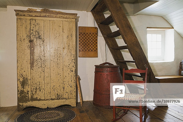 Antique Rocking Chair  Armoire  Stairs Leading To The Attic And Other Furnishings In The Master Bedroom Of An Old Canadiana (Circa 1840) Cottage Style Residential Fieldstone Home  Quebec  Canada. This Image Is Property Released For Calendar  Book  Magazin
