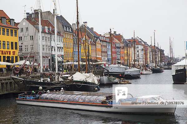 'Nyhavn  the famous waterfront canal in Copenhagen with colourful seventeenth and eighteenth century townhomes lining the canal at dusk; Copenhagen  Denmark'