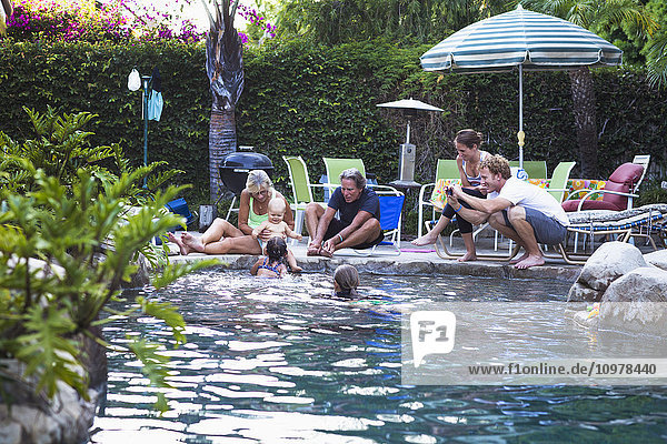 'A family enjoys an afternoon in the pool on a sunny afternoon; Fountain Valley  California  United States of America'