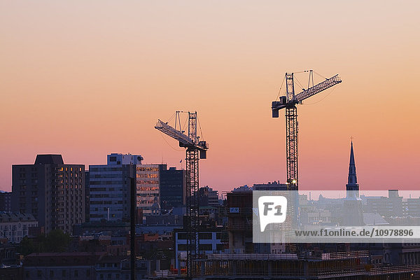 'Construction work cranes towering over the city skyline at dawn; Montreal  Quebec  Canada'