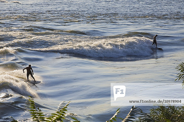 'Surfers riding the rapids on the Saint Lawrence River near Cite-du-Havre; Montreal  Quebec  Canada'