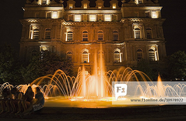 'Water fountain illuminated at dusk in Place Vauquelin in Old Montreal; Montreal  Quebec  Canada'