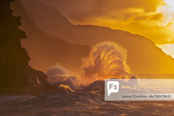 'Surf crashes on the Na Pali coast at sunset; Kauai  Hawaii  United States of America'