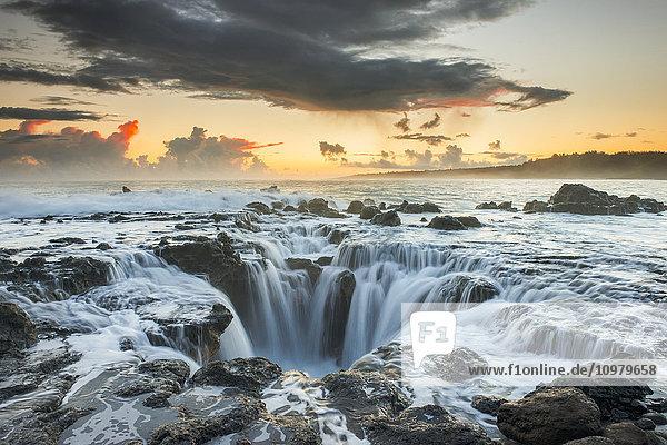 'Surf spills into a hole in a rock outcrop on the east side of Kauai; Kauai  Hawaii  United States of America'