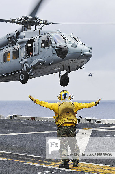 'A crewman onboard the USS Peleliu (LHA-5) guides a MH-60S Knighthawk helicopter in for a landing; Hawaii  United States of America'