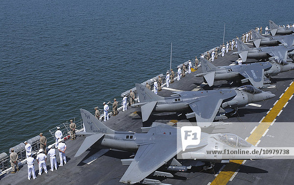 'Sailors and marines onboard the USS Peleliu (LHA-5) ''man the rails'' on the flight deck as the ship leaves port; San Diego  California  United States of America'
