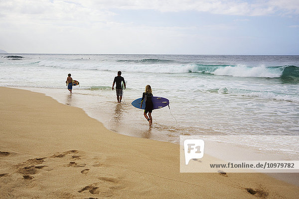 'Three young surfers walk along the beach  Pipeline; Oahu  Hawaii  United States of America'