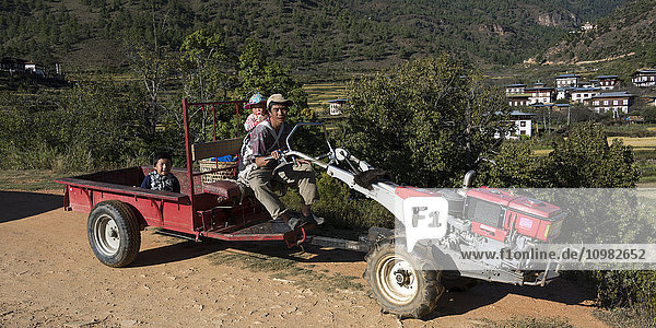 'A father with his young children riding on a piece of farm equipment; Paro  Bhutan'