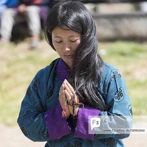 'A young buddhist woman praying; Thimphu  Bhutan'