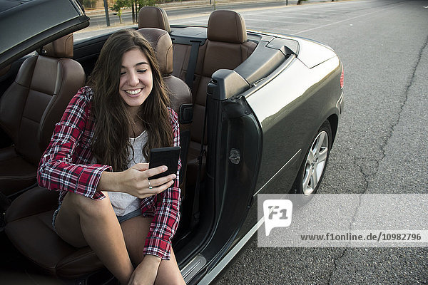 Lächelnde junge Frau sitzt im Cabrio und schaut auf das Smartphone.