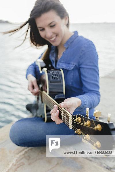 Lächelnde junge Frau sitzt auf dem Dock und spielt Gitarre.