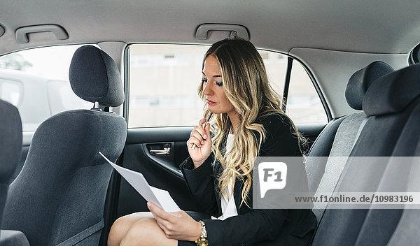 Geschäftsfrau bei der Bearbeitung von Dokumenten im Auto