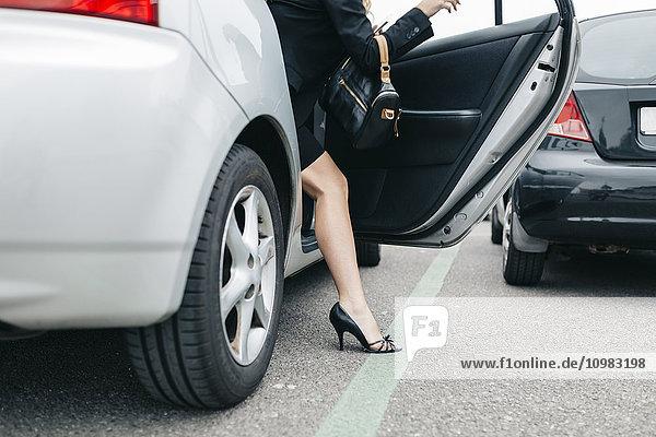 Frau mit hohen Absätzen beim Aussteigen aus dem Auto