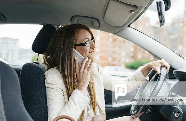 Geschäftsfrau am Handy im Auto