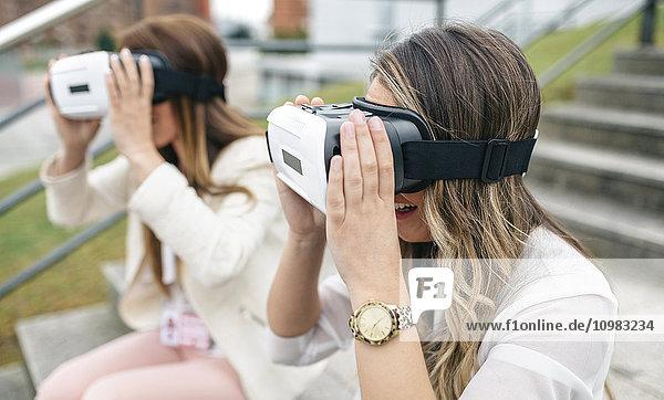 Zwei Frauen haben Spaß mit einer VR-Brille im Freien