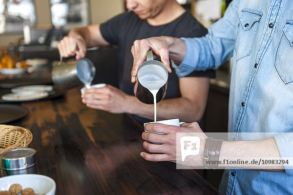 Zwei Männer bereiten Kaffee mit Milch in einem Café zu.