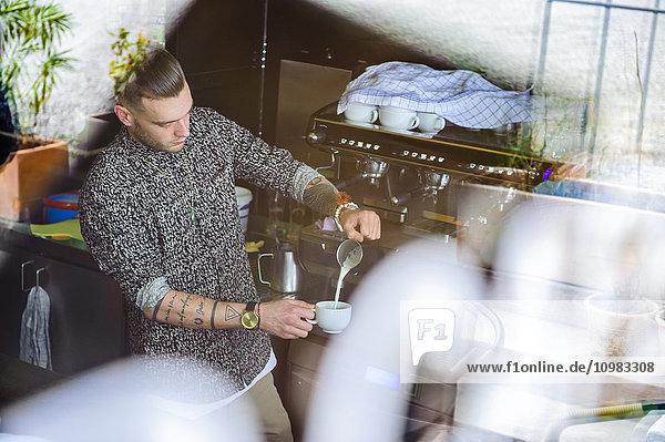 Junger Mann bereitet Kaffee mit Milch in einem Café zu.