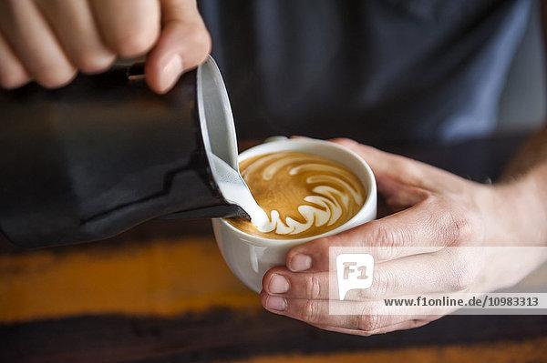 Barista bereitet Cappuccino in einem Café vor
