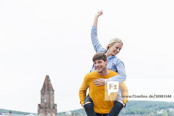 Glücklicher junger Mann  der seine Freundin huckepack trägt.
