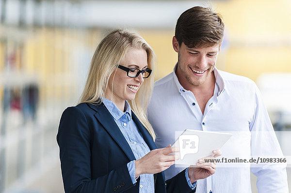 Lächelnder Mann und Frau beim Betrachten des digitalen Tabletts im Freien
