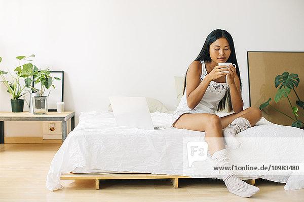 Junge Frau sitzt auf dem Bett und trinkt Kaffee.