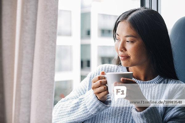 Junge Frau mit Tasse Kaffee vor geöffnetem Fenster