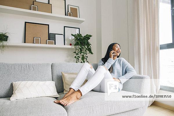 Lachende junge Frau sitzt zu Hause auf der Couch und telefoniert mit dem Handy.